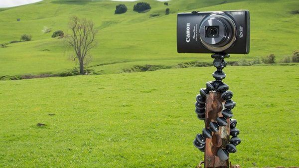 Camera mounted on a flexible tripod in the middle of a field shooting video